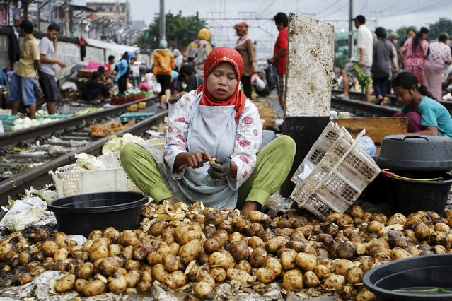 A woman peels potatoes for sale at a market located along a railway line in West Jakarta, Indonesia March 1, 2016. (Photo by Garry Lotulung/Reuters)