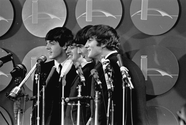 The four members of Britain's young singing group, the Beatles, stand in front of the microphones in the press room of Kennedy International Airport on February 7, 1964 during a press conference following their arrival. (Photo by AP Photo)