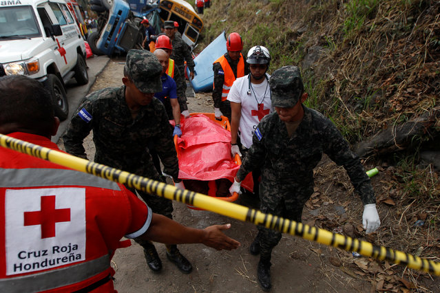 Soldiers and members of the red cross carry a dead body after a crash between a bus and a truck on the outskirts of Tegucigalpa, Honduras, February 5, 2017. (Photo by Jorge Cabrera/Reuters)