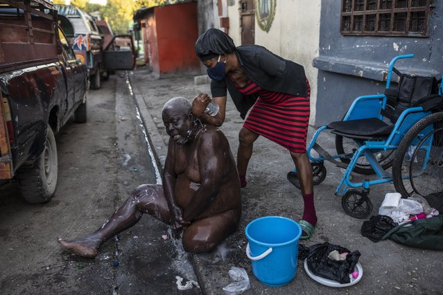 Marie Joseph bathes her friend Jean Robert outside a shelter for the internally displaced where they live due to police violence in Port-au-Prince, Haiti, Thursday, September 16, 2021. Most of the population of Port-au-Prince has no access to basic public services, no drinking water, electricity or garbage collection. (Photo by Rodrigo Abd/AP Photo)