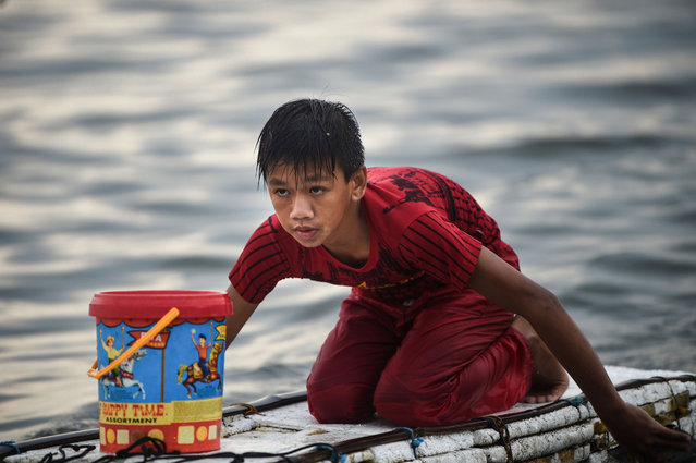 In this photo taken on March 16, 2019, 13-year-old Reymark Cavesirano paddles his borrowed makeshift craft made from styrofoam to fishing boats anchored at the mouth of Manila Bay off Navotas City in suburban Manila. He has been doing this job since he was 10 years old. (Photo by Ted Aljibe/AFP Photo)