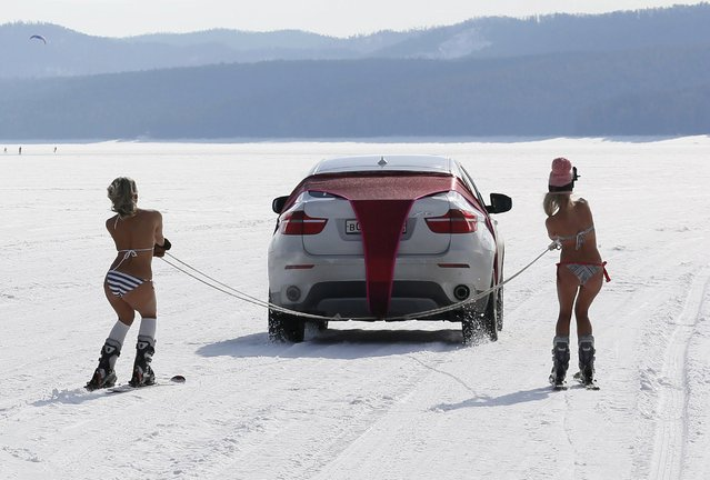 "Bikini-clad women ski as they are led by a car during a performance on the frozen Yenisei River outside Krasnoyarsk, Siberia, Russia, March 20, 2016. The performance, entitled ""Siberian Spring's Strings"" and created with the participation of artist Vasily Slonov, marked the day of spring equinox (vernal equinox), according to organizers. (Photo by Ilya Naymushin/Reuters)"