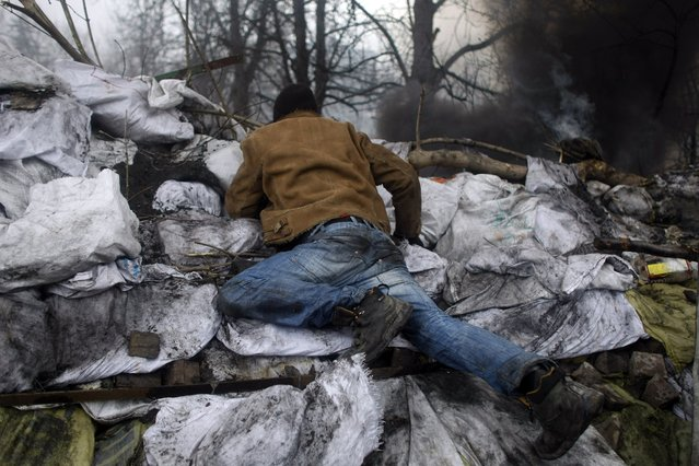 An anti-government protester scans an area behind barricades on the outskirts of Independence Square in Kiev, Ukraine, Thursday, February 20, 2014. (Photo by Marko Drobnjakovic/AP Photo)