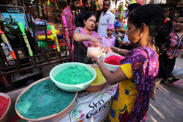 Indian women vendors pack powdered color for sale at a shop on the eve of the Holi festival in Amritsar, India, 22 March 2016. The tradition of Holi, also known as the Festival of Colors, heralds the beginning of spring and will be celebrated on 23 March this year across the country. (Photo by Raminder Pal Singh/EPA)