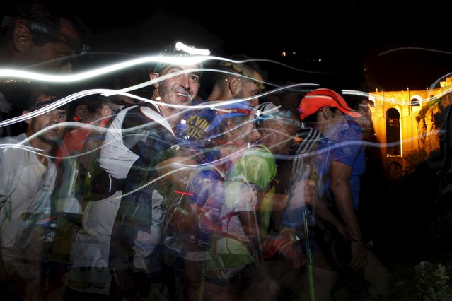 "Trails of headlamps are seen in the night as runners make their way to the finish line, in front of ""Puente Nuevo"" (New Bridge), as they participate in the XVIII 101km international competition in Ronda, southern Spain, May 10, 2015. (Photo by Jon Nazca/Reuters)"