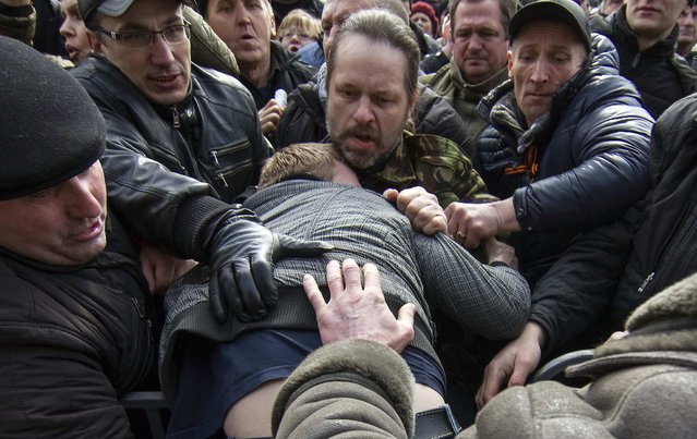 Pro-Russian protesters clash with a supporter of Ukraine's new government during a rally in central Donetsk March 1, 2014. Russian President Vladimir Putin has asked the upper house of parliament to approve sending armed forces to Ukraine's Crimea region, the Kremlin said in a statement on Saturday. The Crimea region has a majority ethnic Russian population. (Photo by Reuters/Stringer)