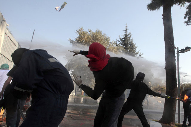 A masked demonstrator throws a petrol bomb towards the police during a protest at the University of Santiago, in Santiago, Chile, Thursday, May 14, 2015. (Photo by Luis Hidalgo/AP Photo)