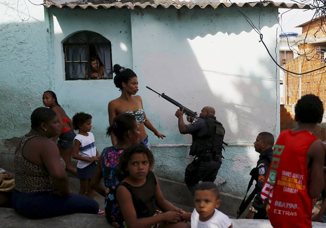 Residents observe as policemen take up position near an area where two men were found dead on top of the Sao Carlos slums complex in Rio de Janeiro May 15, 2015. According to residents of the complex, there is an ongoing war between drug dealers in the region and these two men were killed by the police during a police operation in the same area the previous night. (Photo by Ricardo Moraes/Reuters)
