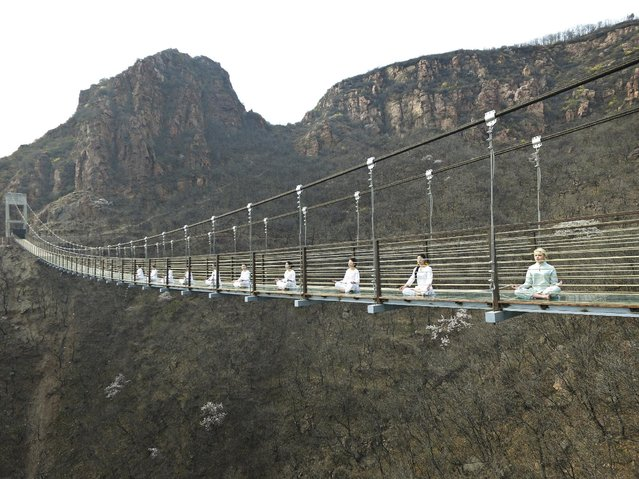 Women perform yoga on a glass suspension bridge as a way to attract tourists in Fuxishan, Zhengzhou, Henan province, March 30, 2016. (Photo by Reuters/China Daily)