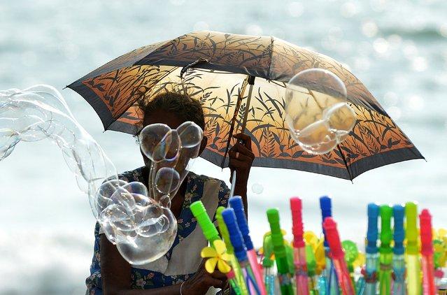A Sri Lankan vendor sells bubble liquid on the Galle Face promenade in the heart of the Sri Lankan capital of Colombo on April 19, 2015. (Photo by Ishara S. Kodikara/AFP Photo)