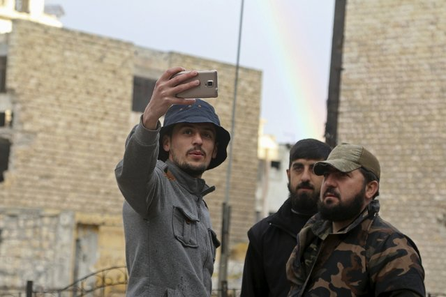 A man takes a selfie with rebel fighters in front of a rainbow in the rebel held area of Aleppo's Salah al-Din neighbourhood, Syria March 28, 2016. (Photo by Abdalrhman Ismail/Reuters)