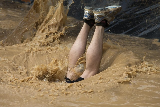 A participant dives into a mud pool while taking part in the Mud Day athletic event in Toledo, Spain, Saturday, May 23, 2015. (Photo by Paul White/AP Photo)
