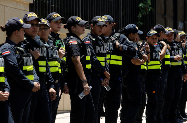 Police officers stand guard during a protest of taxi drivers against a proposal to legalize ride-hailing service Uber in San Jose, Costa Rica April 14, 2016. (Photo by Juan Carlos Ulate/Reuters)