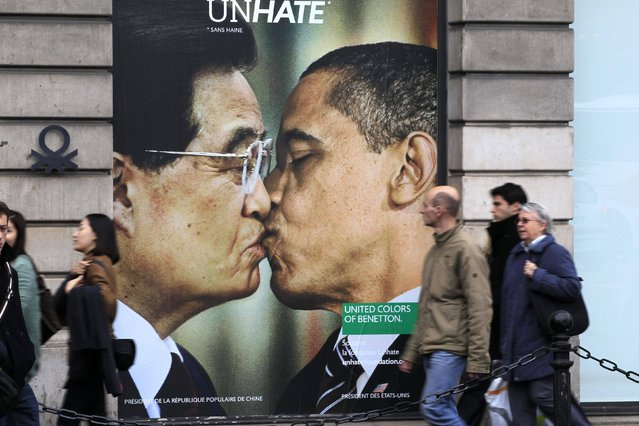 People walk past a billboard of a photo montage with U.S. President Barack Obama kissing China's President Hu Jintao displayed on a Benetton store in Paris November 17, 2011. Photo montages of the advertising campaign, which Benetton says supports the Unhate Foundation, show world leaders kissing each other on the mouth. (Photo by Charles Platiau/Reuters)
