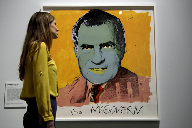"A British Museum representative poses for photographs next to ""Vote McGovern"" by Andy Warhol which features in ""The American Dream: pop to the present"" exhibition during a media photocall at the British Museum in London, Monday, March 6, 2017. (Photo by Matt Dunham/AP Photo)"