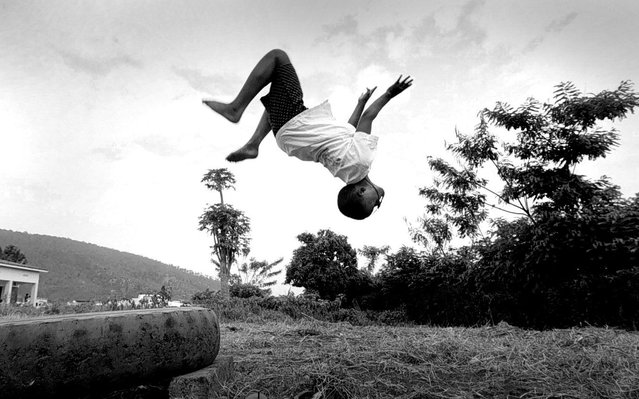 Nyirandinabo Nzungu, 12, does a backflip off an old tire at Gisimbe orphanage in Kigali. She is a refugee who lost her mother after fleeing from Katale camp in Zaire. Her father was killed in the war; 1996. (Photo by Carol Guzy/The Washington Post)