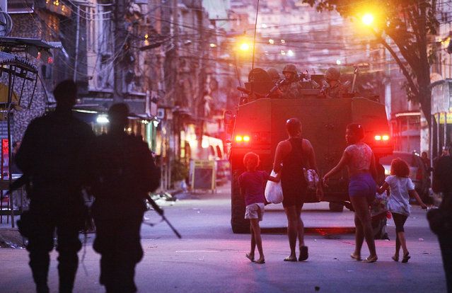 People walk as Brazilian Navy soldiers in a tank enter the unpacified Complexo da Mare, one of the largest 'favela' complexes in Rio, on March 30, 2014 in Rio de Janeiro, Brazil. The Brazilian government has deployed federal forces to occupy the group of violence-plagued slums ahead of the June 12 start of the 2014 FIFA World Cup. (Photo by Mario Tama/Getty Images)
