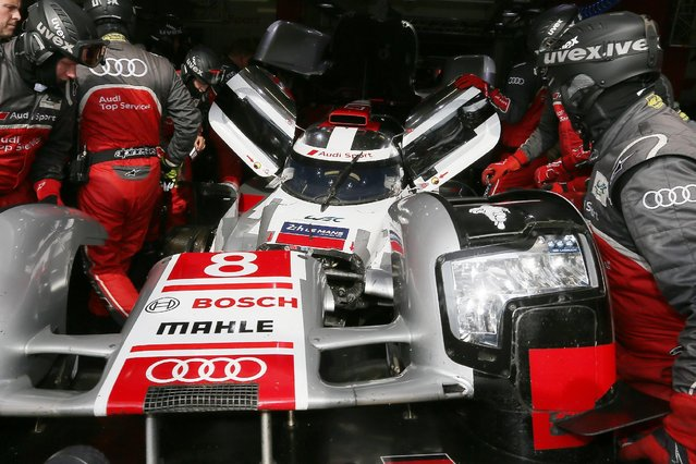Mechanics repair the Audi R18 E-TRON Quattro No8 of driven by Lucas Di Grassi of Brazil, Loic Duval of France and Britain's Oliver Jarvis during a stop in the pits during the 83rd 24-hour Le Mans endurance race, in Le Mans, western France, Saturday, June 13, 2015. (AP Photo/David Vincent)