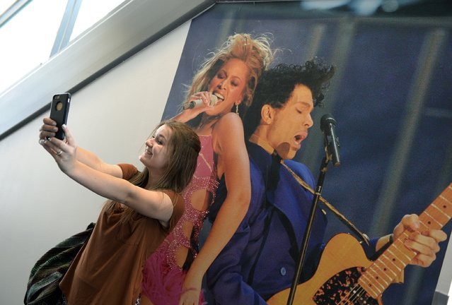 Alexandria Pivarnyik, 17, takes a selfie with a photograph of Prince and Beyonce performing at the 46th Grammy Awards in 2004 placed at the Grammy Museum in memory of musician Prince on April 21, 2016, in Los Angeles, California. (Photo by Kevork Djansezian/Getty Images)