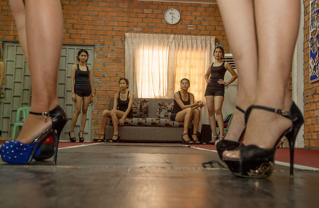 Students from the Sun Model agency are trained on the catwalk while fellow students look on during a training session at the school on March 31, 2014 in Phnom Penh, Cambodia. (Photo by Omar Havana/Getty Images)