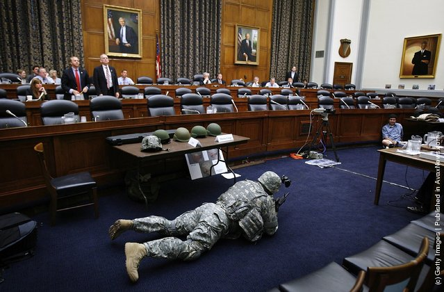 Sgt. First Class Jerry Lutz from Fort Belvior, Virginia, demonstrates how early versions of the Army's combat helmets made it difficult to see from a prone shooting postion during a hearing of the US House Armed Services Committee Tactical Air and Land Forces Subcommittee on Capitol Hill