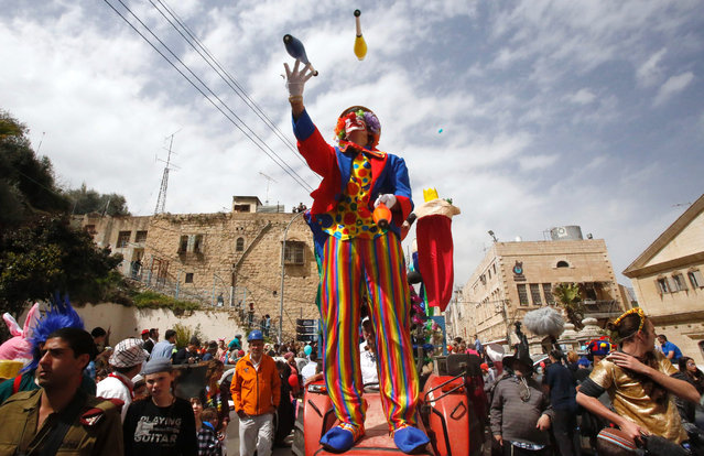 Israeli settlers take part in a parade to celebrate the Jewish holiday of Purim in al-Shuhada Street, in the West Bank town of Hebron, on March 12, 2017. The carnival-like Purim holiday is celebrated with parades and costume parties to commemorate the deliverance of the Jewish people from a plot to exterminate them in the ancient Persian Empire 2,500 years ago, as recorded in the Biblical Book of Esther. (Photo by Hazem Bader/AFP Photo)
