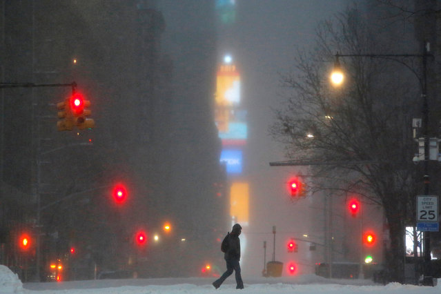 Times Square is seen in the background as a man walks along West 59th street in falling snow in Manhattan, New York, U.S., March 14, 2017. (Photo by Andrew Kelly/Reuters)