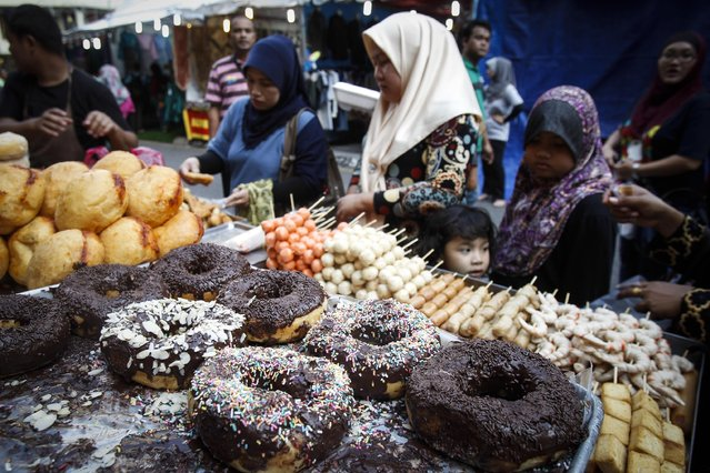 Malaysian Muslim women buy foods for breakfast at a bazaar during Islam's holy month of Ramadan, in Kuala Lumpur, Malaysia, Saturday, June 27, 2015. Muslims throughout the world are marking the month of Ramadan, the holiest month in the Islamic calendar during which devotees fast from dawn till dusk. (Photo by Joshua Paul/AP Photo)