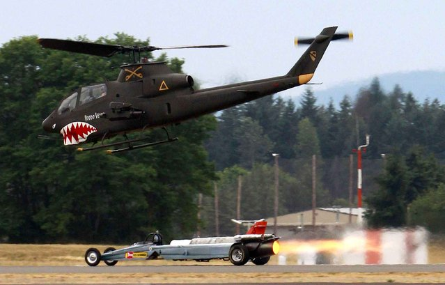 The Smoke & Thunder Jet Car driven by Bill Braack pulls away late on the runway, getting past the Olympia Flight Museum's AH-1 Cobra piloted by Brian Reynolds, the museum's founder, on Sunday, June 28, 2015, during the Olympic Air Show in Olympia, Wash. (Photo by Steve Bloom/The Olympian via AP Photo)