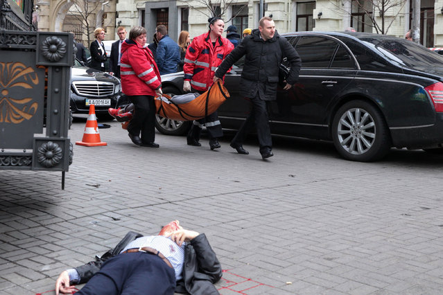 """Medical workers carry the alleged gunman wounded after he shot dead former Russian MP Denis Voronenkov in central Kiev on March 23, 2017. Ukrainian President blamed Russia for the murder of Voronenkov, who moved to Ukraine last year and was wanted by Russia for fraud, saying it was an """"act of state terrorism"""". (Photo by Sergei Supinsky/AFP Photo)"""