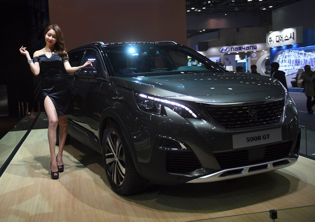 A South Korean model poses with Peugeot 5008GT during a press preview of the Seoul Motor Show in Goyang, northwest of Seoul, on March 30, 2017. South Korea's largest international auto show will open on March 31, with a total of 27 brands showing their latest cars and concepts. (Photo by Jung Yeon-Je/AFP Photo)