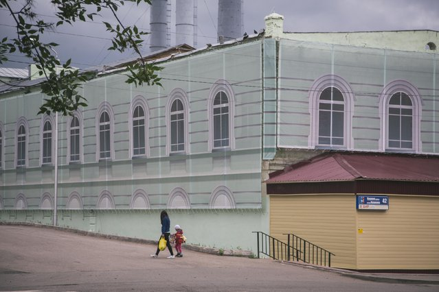 In this photo taken on Sunday, July  5, 2015, a woman and her child walk along an old house covered with  illustrated sheeting to give the facade an improved appearance, in downtown Ufa, Russia. (Photo by Vadim Braydov/AP Photo)