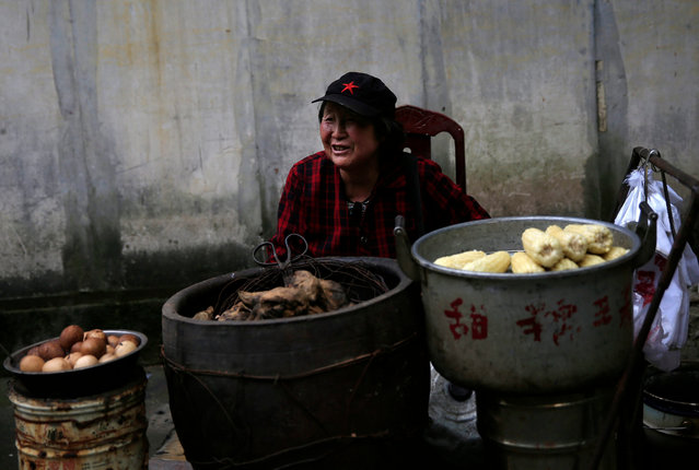"""Chinese food seller Liu Fuxiu sells eggs, sweet potatoes and corn at her stall outside the """"Water Dripping Cave"""" compound, where Mao Zedong stayed briefly for 11 days in 1966 and is thought to have contemplated the start of the Cultural Revolution there in Shaoshan, Hunan Province in central China, 28 April 2016. (Photo by How Hwee Young/EPA)"""