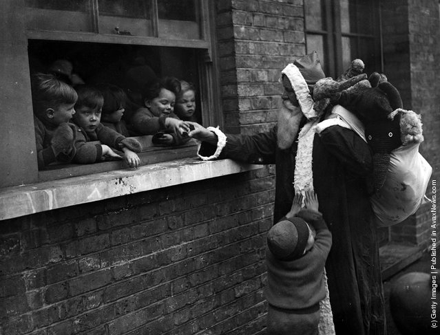 1931: Father Christmas delivering presents to the Children's Aid and Adoption Society at Leytonstone, London