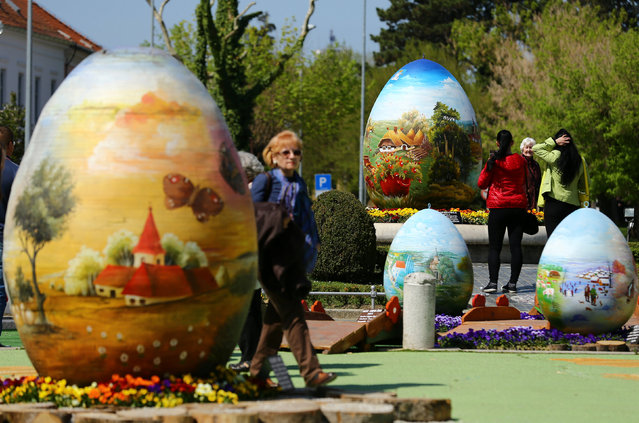 People walking between a two-metre-high Easter eggs painted in the traditional naive art style exhibition in Koprivnica, Croatia, April 9, 2017. The project, which started ten years ago, involves painters decorating two-metre-tall polyester eggs, which are then sent to cities in the country and abroad to be displayed in public squares in time for Easter festivities. (Photo by Antonio Bronic/Reuters)