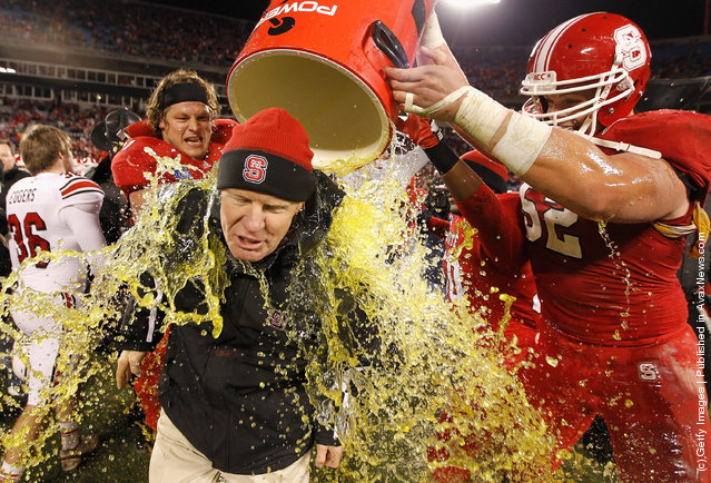 Head coach Tom O'Brien of the North Carolina State Wolfpack is dunked in Gatorade after defeating the Louisville Cardinals 31-24 at Bank of America Stadium
