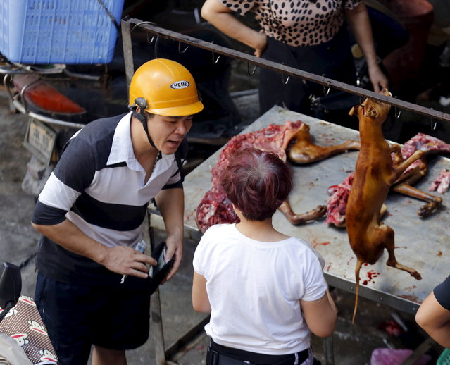 A man buys dog meat from a vendor at a dog meat market in Yulin, Guangxi Autonomous Region, June 21, 2015. (Photo by Kim Kyung-Hoon/Reuters)