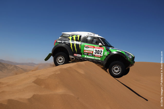 Stephane Peterhansel of France drives his Mini over a sand dune during stage seven of the 2012 Dakar Rally