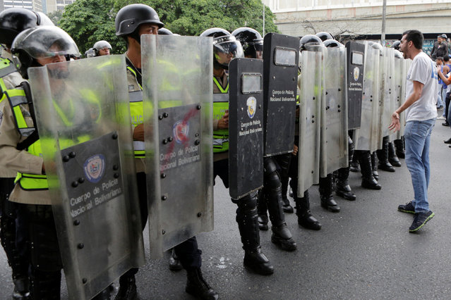 An opposition supporter shouts towards riot policemen in a rally to demand a referendum to remove President Nicolas Maduro in Caracas, Venezuela, May 11, 2016. (Photo by Marco Bello/Reuters)