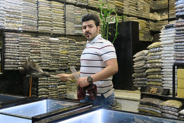 A shopkeeper preparing to welcome new customers dusts his stock of buttons in Tehran's Grand bazaar, Iran May 3, 2016. (Photo by Marius Bosch/Reuters)