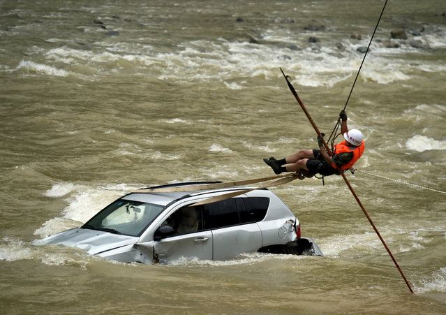 A rescue worker tries to remove a trapped car from a flooded river in Chongqing Municipality, July 15, 2015. According to local media, more than ten vehicles fell into the river in a landslide caused by a heavy rainfall on Tuesday. (Photo by Reuters/Stringer)