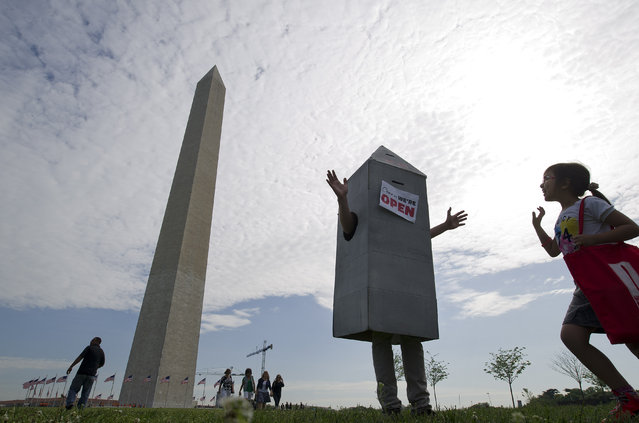 "Wearing a Washington Monument costume, Steven Avila, center, greets Alexandra Smith, 7, of Glen Burnie, MD, right, prior to the ""Celebration of the Reopening of the Washington Monument"" on Monday May 12, 2014 in Washington, DC. The iconic landmark had been closed to the public since a earthquake damaged the structure in 2011. (Photo by Matt McClain/The Washington Post)"