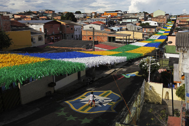 A boy rides his bicycle along Third Street of the Alvorada neighbourhood which is decorated for the 2014 World Cup in Manaus, one of the tournament's host cities, May 17, 2014. The World Cup will be held in 12 cities across Brazil from June 12 through July 13. (Photo by Bruno Kelly/Reuters)