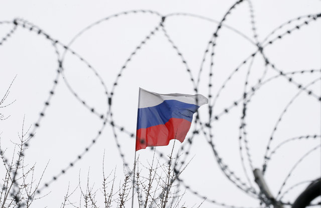 The Russian flag is seen through barbed wire as it flies on the roof of the Russian embassy in Kiev, Ukraine on March 26, 2018. (Photo by Gleb Garanich/Reuters)