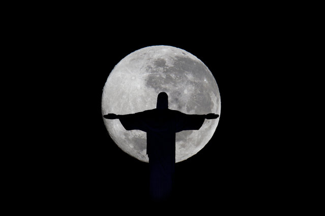 A full moon is seen behind the Christ the Redeemer statue in Rio de Janeiro, Brazil, early Wednesday July 4, 2012. (Photo by Felipe Dana/AP Photo)
