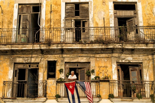 "Photographer Dotan Saguy visited Cuba expecting to find resentment toward Americans, but he says that, instead, ""Every Cuban I met was warm and welcoming despite me being an American"". Here: A retired man stands at the window of his one-bedroom apartment on Seaport Avenue in Old Havana, Cuba, May 2, 2016. He proudly displays U.S. and Cuban flags side by side to welcome visitors from the first American cruise ship to enter the port of Old Havana in decades. (Photo by Dotan Saguy)"