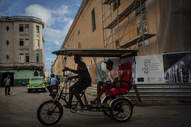 In this November 9, 2019 photo, a bicycle taxi driver navigates his client past buildings under restoration in Havana, Cuba. (Photo by Ramon Espinosa/AP Photo)