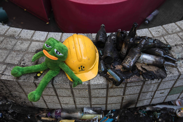 A stuffed toy depicting Pepe the Frog, a character used by pro-democracy activists as a symbol of their struggle, is seen next to a helmet and burnt glass bottles at the Hong Kong Polytechnic University in the Hung Hom district in Hong Kong on November 22, 2019. Hardline Hong Kong protesters held their ground on November 21 in a university besieged for days by police as the US passed a bill lauding the city's pro-democracy movement, setting up a likely clash between Washington and Beijing. (Photo by Dale de la Rey/AFP Photo)