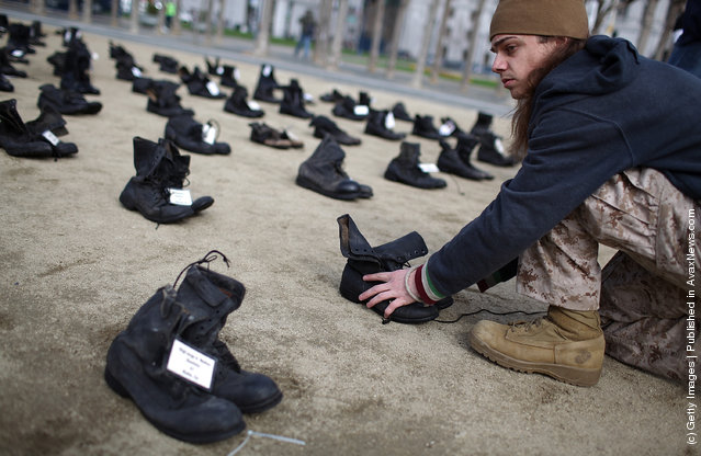 Iraq war veteran Scott Olsen adjusts rows of combat boots that are part of the Eyes Wide Open exhibit in front of San Francisco City Hall