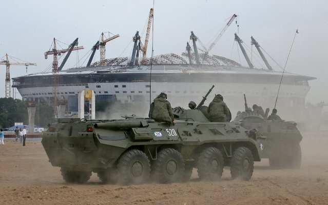 Marines' APCs drive toward the construction site of the new Zenit Stadium, which will host matches of the 2018 World Cup, after a military show during celebration of Navy Day at the Finnish Gulf coast in St.Petersburg, Russia, Sunday, July 26, 2015. (Photo by Dmitry Lovetsky/AP Photo)